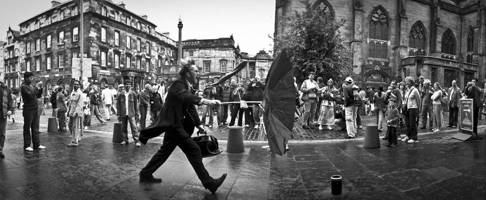 immagine: uomo con ombrella strappata dal vento
